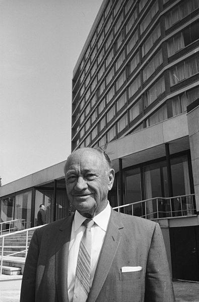 black and white picture of Conrad Nicholson Hilton, in the background you can see his hotel in Amsterdam.