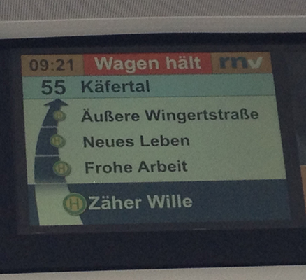 "Photo of a stop display of bus number 55 in Mannheim, you can read the next three stops: ""Zäher Wille"" (tenacious will), ""Frohe Arbeit"" (happy work) and ""Neues Leben"" (new life)."