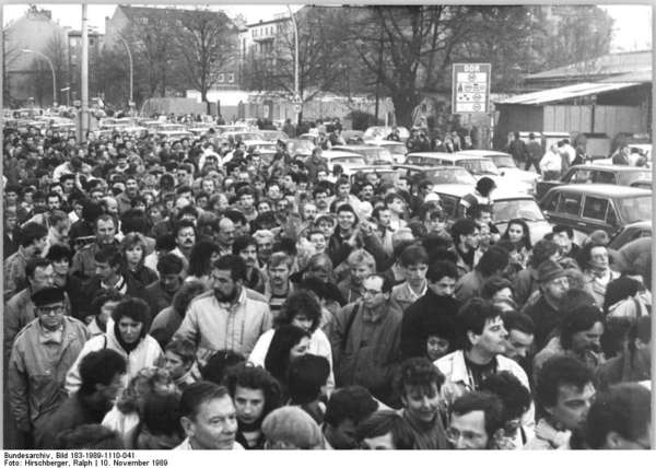 Black-and-white photograph of a mass of people (including cars) that clusters at the border crossing Invalidenstrasse in Berlin on 10 November 1989.