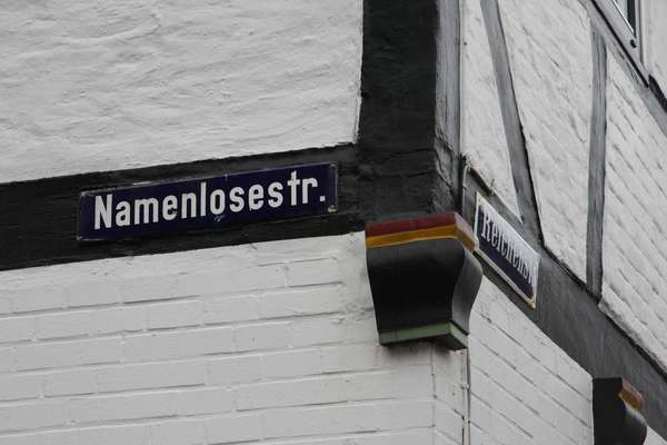 Street sign of Namenlose Straße (Nameless Street) in Glückstadt on a house on the corner to Reichenstraße.
