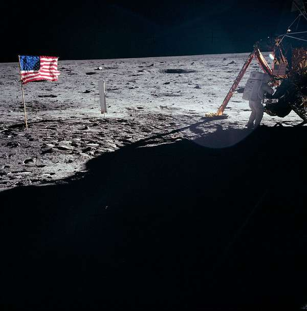 Picture of Neil Armstrong working on the moon near lunar module Eagle, on the left side of the picture you can see the American flag.