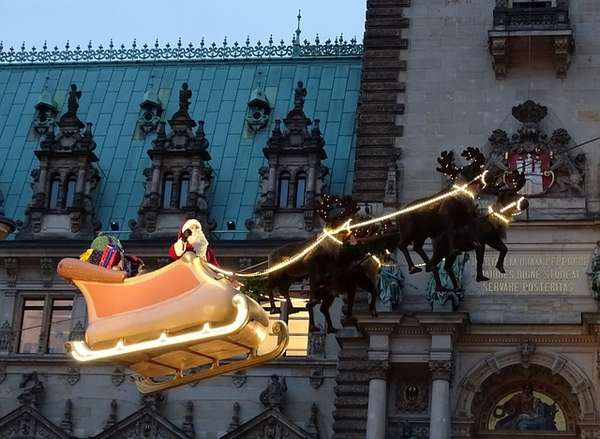 Santa Claus flies above Hamburg's city hall Christmas market in his sleigh